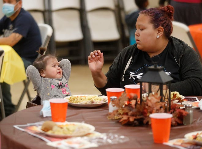 Marissa Vizcaino and her 2-year-old daughter Everlee Vizcaino eat their Thanksgiving dinner at the Salvation Army Thursday.
