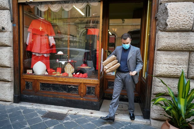 A shop attendant walks out of the Gammarelli clerical clothing shop in Rome on Thursday.