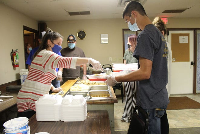 A volunteer serves Thanksgiving dinner to a waiting diner at the Macomb Eagles Club on Thursday.