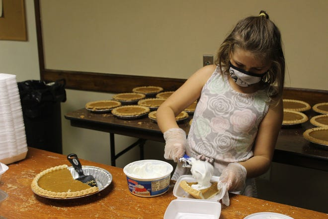 Lillyonna Martin scoops whipped topping onto a slice of pumpkin pie destined for a carryout Thanksgiving meal. The Eagles Club in Macomb continued its annual free Thanksgiving meal tradition via carryout rather than dine-in due to COVID-19 restrictions.
