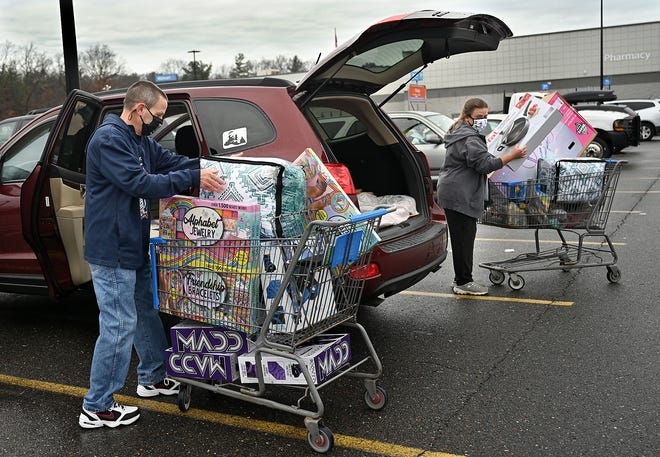Keith Crozier, left, and his daughter Kerri Lanctot, both of Bellingham, load up the minivan with a bicycle and other  gifts at WalMart in Bellingham on Black Friday, Nov. 27, 2020.