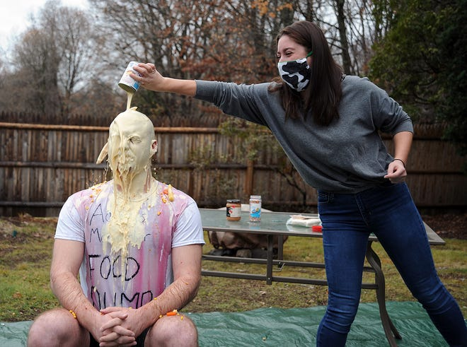 "A can of expired evaporated milk covers Adam Levine, of Framingham, who raised more than $10,000 for men's mental health with a ""food dump"" on Friday, Nov. 27, 2020. His twin sister, Hannah, handled the dumping."