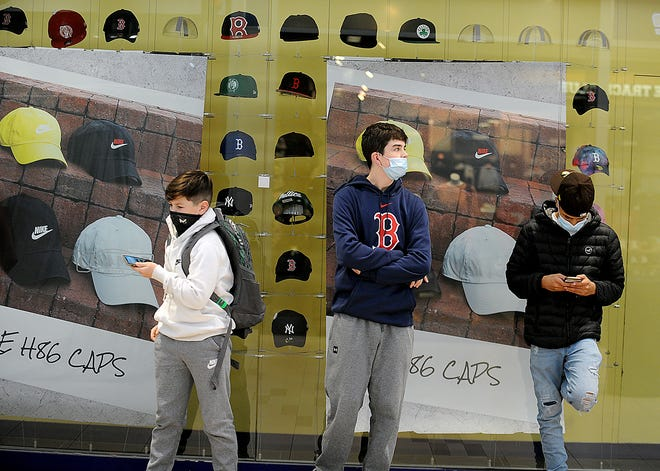 From left, James Conley, 14, of Natick; Brendan Dolan, 17, of New York; and Daniel Rodrigues, 16, of Framingham, wait for the Champs store to open at 7 a.m. in the Natick Mall on Black Friday, Nov. 27, 2020.