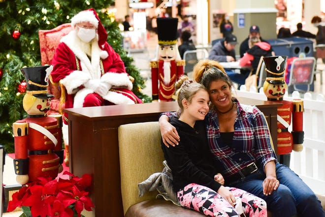 Utica resident Antoinette Placanica and her daughter Gia get a photo taken with Santa during Black Friday at Sangertown Square in New Hartford.
