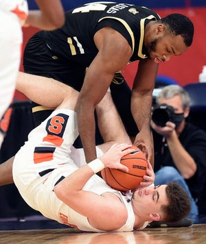 Bryant forward Hall Elisias (34) and Syracuse guard Joseph Girard III (11) battle for the ball during the first half Friday at the Carrier Dome. Girard hit a three-pointer late in the second half to help Syracuse earn an 85-84 win.