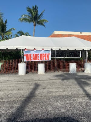 A tent is set up outside Double Roads Tavern for outdoor dining and music in Jupiter.