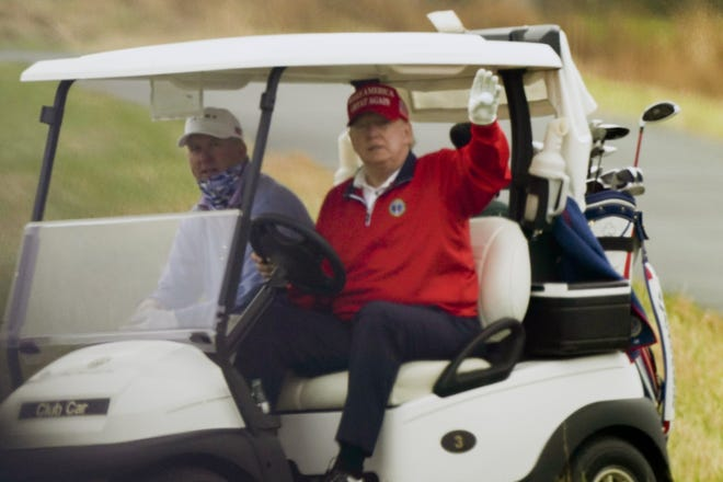 President Donald Trump waves from a golf cart as he plays golf at Trump National Golf Club last week in Sterling, Va. (AP Photo/Alex Brandon)