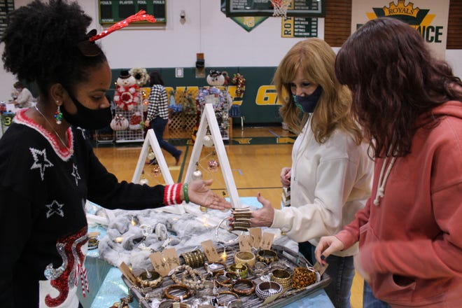 TK's Jewelry & Essentials owner Teherra Kearse of Prince George shows Sheila Shannon and her sixteen-year-old daughter Gracie of Disputanta items on display at the Tinsel Town Holiday Bazaar held at Prince George High School on Nov. 14, 2020.