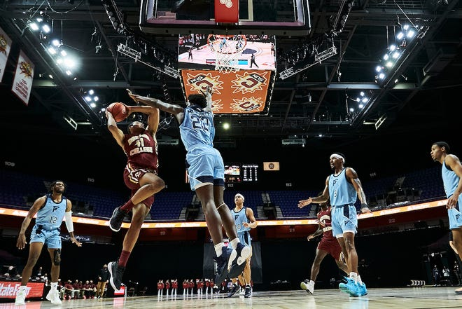 URI's Makhi Mitchell (21) defends against Boston College Thursday night  in theconsolationgame of the 2K Empire Classic at Mohegan Sun Casino.