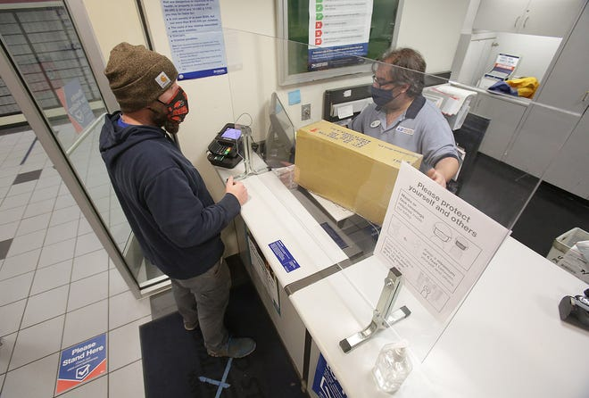 Josh Lenartowitcz ships a package with the help of window clerk Nick Morrison at the Massillon Post Office. Workers at the Post Office have seen an increase in traffic and the expect it to get worse as the holiday approaches.