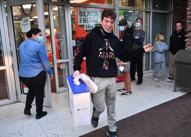 Ethan Clements, 18, emerges from the GameStop store in University Town Center, with one of only two PlayStation 5 video game consoles the store had for sale on Friday morning, Nov. 27, 2020.  Clements had to get in line Wednesday at 8pm to be the first in line for the popular game system.