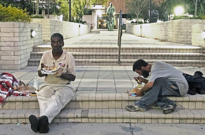 Anthony Dixon eats dinner with another homeless man on the steps of Sarasota's City Hall in March. At the time, the 59-year-old Dixon had recently lost his home.