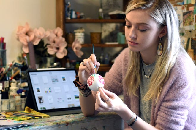 Eden Mills paints an ornament as part of her floral collection at her Art of Eden studio in downtown Burgaw, N.C., Friday, November 27, 2020. Mills produces a wide variety of art including paintings, murals, and jewelry.   [MATT BORN/STARNEWS]