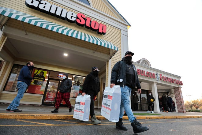 John Santiago and his son John Santiago Jr. are seen leaving Gamestop in Dartmouth with PlayStation 5's after waiting two days to take advantage of the Black Friday deal.