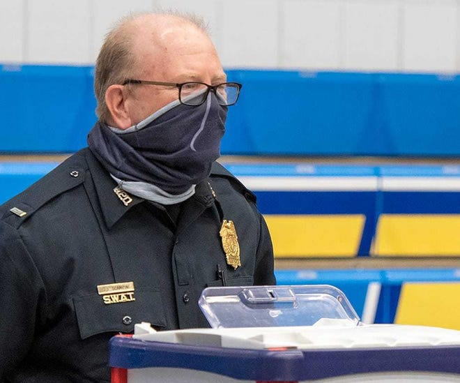 Worcester Police Lt. Joe Scampini wears a mask while he works at a polling place Nov. 1 during early voting.