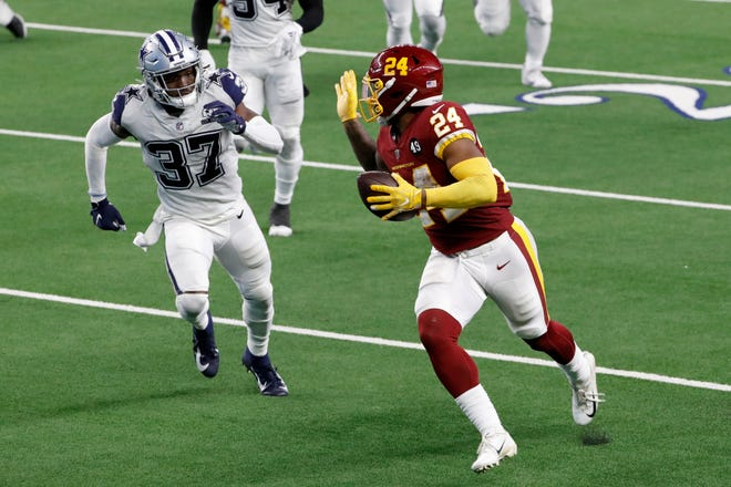 Washington running back Antonio Gibson gestures with his hand as he gets past Dallas safety Donovan Wilson on his way to the end zone for a touchdown during Thursday's game.
