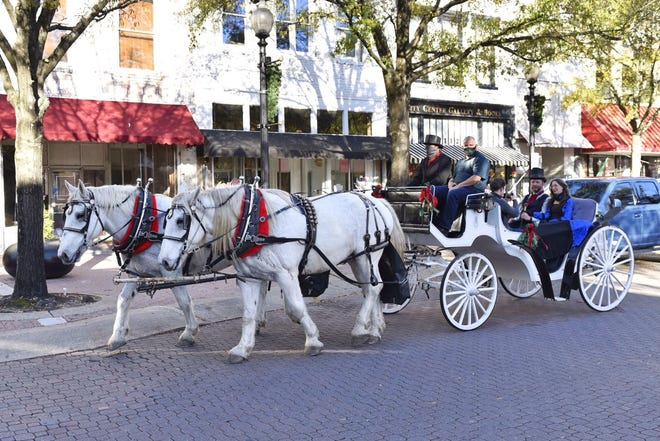 People enjoy carriage rides in downtown Fayetteville on Friday.