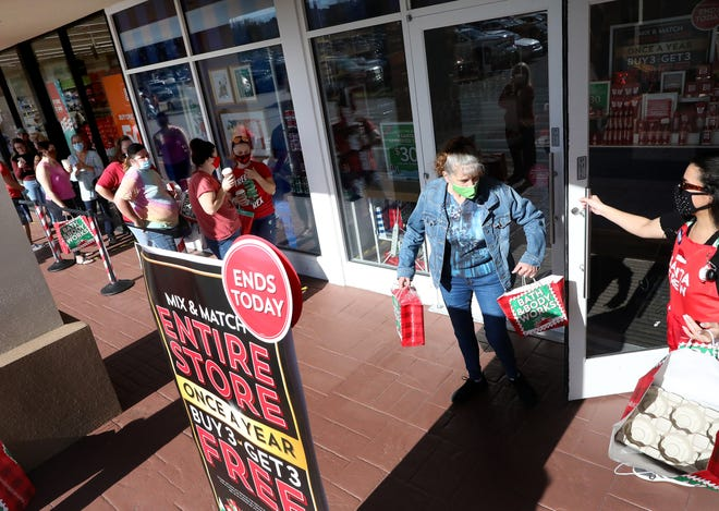 An employee passes out bags to customers waiting in line to enter Bath & Body Works in Butler Plaza on Friday as the store limited capacity to reduce risk of coronavirus transmission.