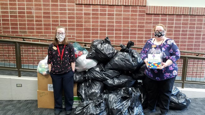 Library staff Elise Thompson and Robyn Matako stand next to nearly 200 pounds of plastic caps and lids, which will be used to make a plastic bench for the community. Pictured, from left: Elise Thomspon and Robyn Matako.