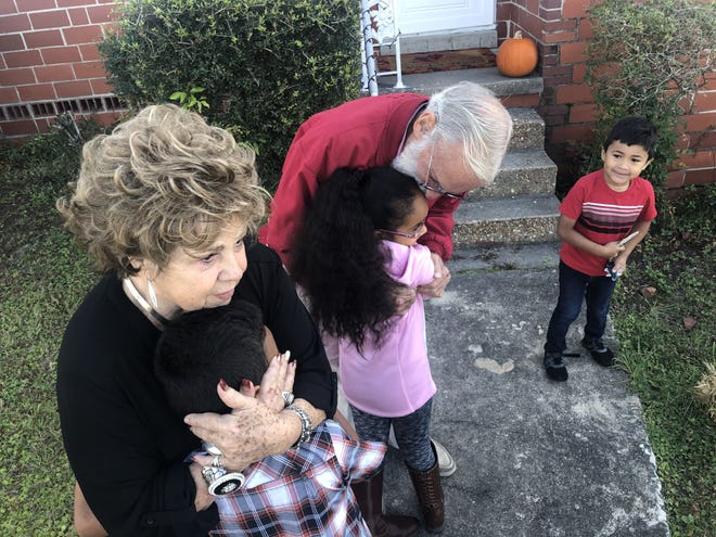 Thomas Hails and Judy Pettit embrace Yudith Bustillo's children —Justin, 7, Rosa, 8, and Harlin, 4. The couple gifted the Bustillo family $1,000 Wednesday to help where needed this holiday season.