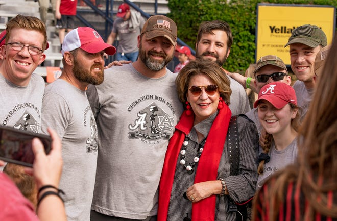 Miss Terry Saban takes photos with members of operation Iron Ruck, who marched from Tuscaloosa to Auburn, before the NCAA SEC football game between the Alabama Crimson Tide and the Auburn Tigers at Jordan-Hare Stadium in Auburn, Ala. on Saturday, Nov. 30, 2019. [Photo/Jake Arthur]