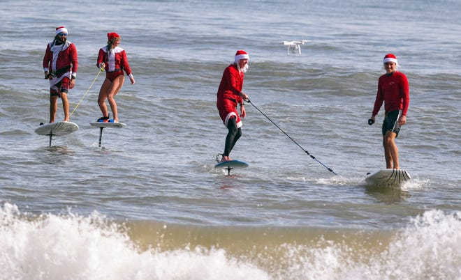 From left to right, electric hydrofoil surfers Billy Bosch, Ashley Nolan, Joe Penovich and Daniel Penovich ride to shore alongside a drone Friday during a Surfing Santas promotional video shoot in Cocoa Beach.