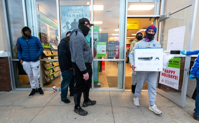 Ben Hoban, 17, of Clarks Summit, Pa., carries his new Sony PlayStation 5 video game console out of a GameStop store on Black Friday,  in Dickson City, Pa.  Friday, Nov. 27, 2020.