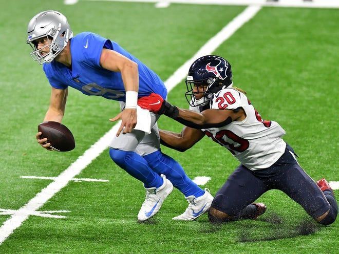 Keamanan kuat Texas Justin Reid (20) memulai pemecatan quarterback Lions Matthew Stafford (9) di kuarter ketiga.