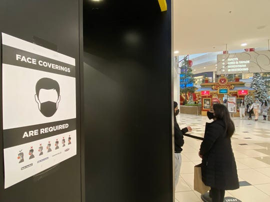 Signs for face coverings were posted on walls of Twelve Oaks Mall on Black Friday.