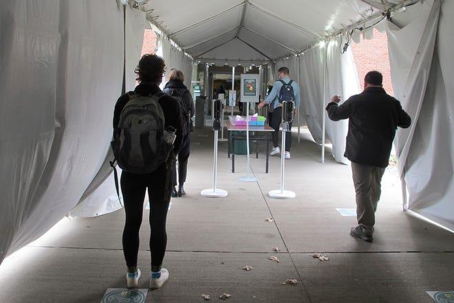 Dalam foto 12 November 2020 ini, mahasiswa Universitas Vermont berjalan melalui tenda menuju lokasi pengujian COVID di kampus di Burlington, Vt.