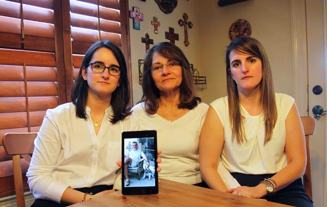 Dalam file foto 15 Februari 2019 ini, Dennysse Vadell duduk di antara putrinya Veronica, kanan, dan Cristina memegang foto digital ayah dan suaminya Tomeu yang saat ini dipenjara di Venezuela, di Katy, Texas.