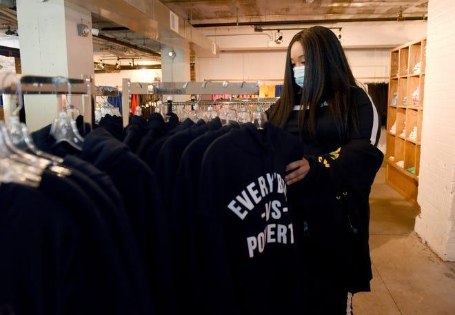 Donya Clowney dari Highland Park berbelanja di toko Detroit vs Everybody pada hari Jumat. Pengecer memulai penjualan Black Friday seminggu lebih awal.