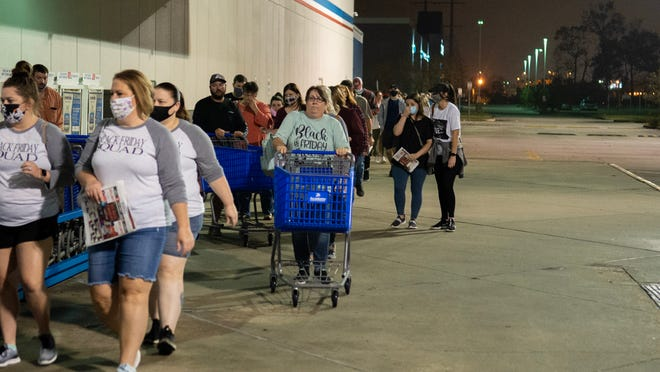 Long lines form in front of businesses in the early hours of Friday to get some of the best deals of the year Friday, Nov. 27, 2020.