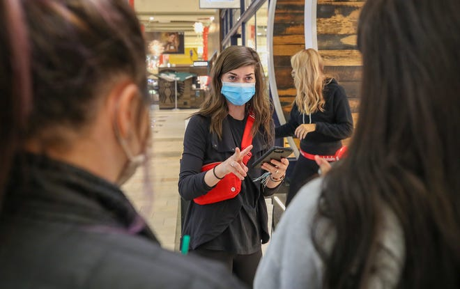 Leah Jo Turner, at Lululemon, checks in shoppers on an app that allows them to be contacted when a spot is open in the store.  Lululemon and other stores are using apps to keep the number of shoppers in the store to certain limits during the Coronavirus pandemic.