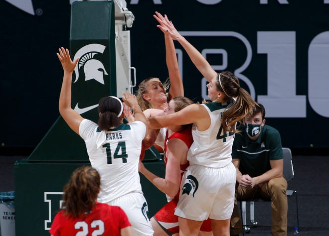Michigan State's Taiyier Parks, left, Tory Ozment, rear, and Kendall Bostic, right, swarm St. Francis' Katie Dettwiller Friday, Nov. 27, 2020, in East Lansing, Mich.