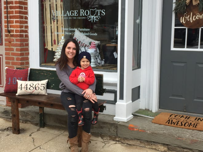 Village Roots co-owner Katie Veletean and her son, 2-year-old Nash, sit outside the new business in Plymouth.