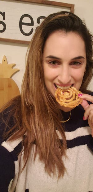 Shaked Ram tries out her zangula, or Jewish funnel cake.