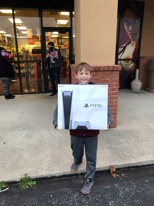 Kenneth Looney emerges from the Mountain Home GameStop with a PlayStation 5 on Friday morning. Looney had camped out in front of the store since 11 a.m. Thursday in order to purchase one of the two PlayStation 5 systems the store had in stock.