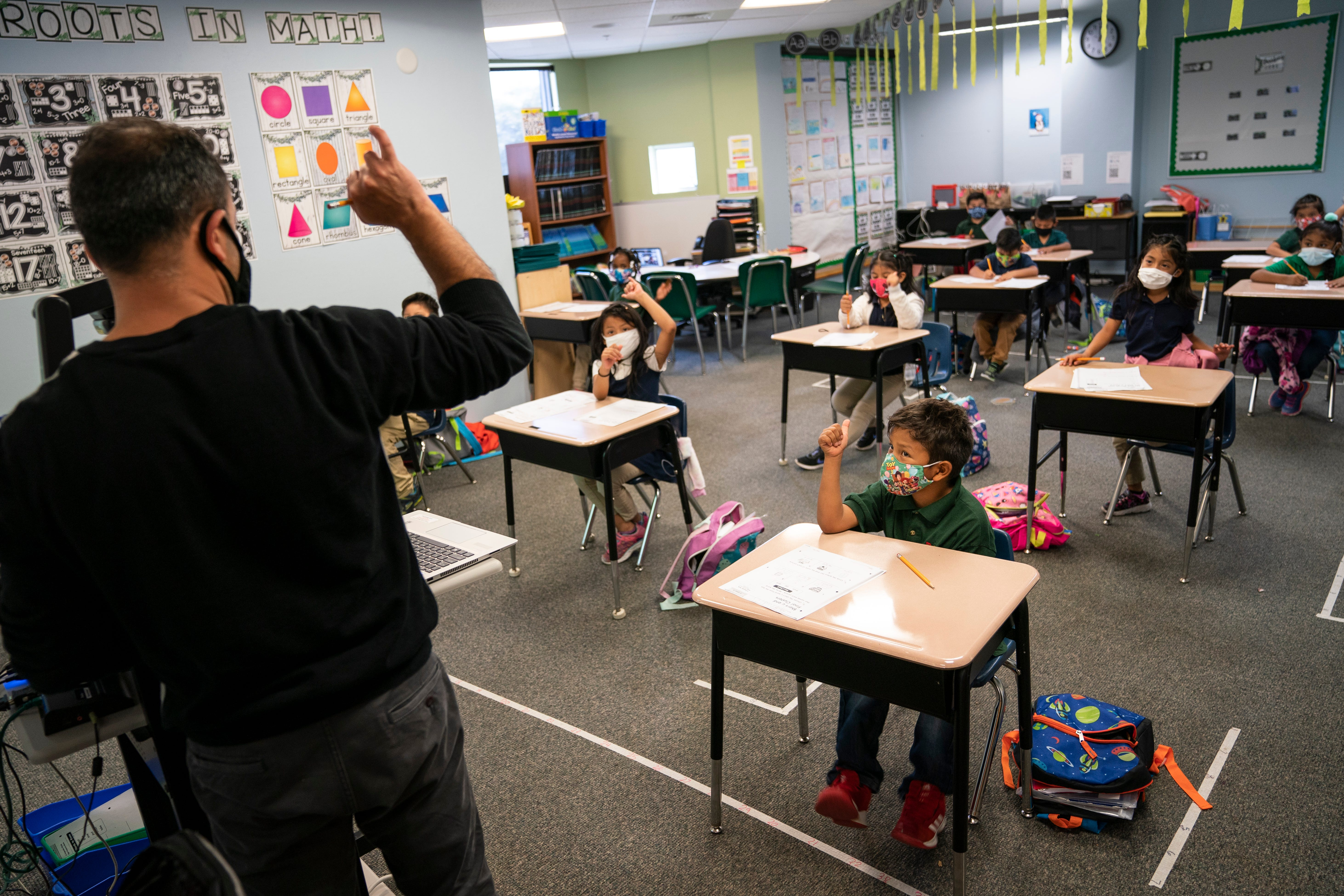 Ozgur Dursun asks his first-graders to hold up their pinkies during a classroom activity at RCMA Immokalee Community School. Migrant students face educational challenges every year as they move back and forth between schools while traveling with their families, but the coronavirus pandemic has created additional challenges and stressors.