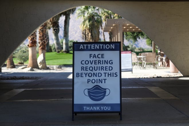 A sign at the entrance to the Tahquitz Creek Golf Resort informs the public of the face covering policy in Palm Springs, November 27, 2020