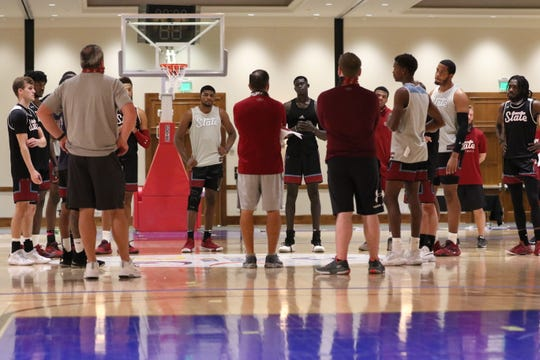 The New Mexico State Aggies talk on their practice court at the Arizona Grand Resort & Spa in Phoenix, where they are temporarily housed.