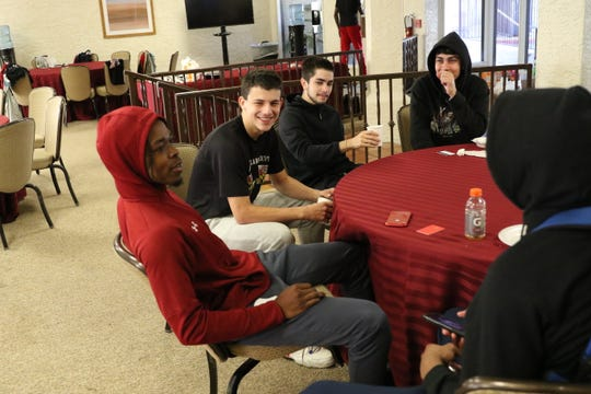 New Mexico State Aggies players and support staff relax in a dining room at the Arizona Grand Resort & Spa, where the basketball team is staying due to COVID-19 restrictions in their home state.