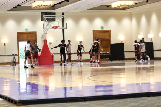 The New Mexico State Aggies basketball team practices on a court installed at the Arizona Grand Resort & Spa in Phoenix.