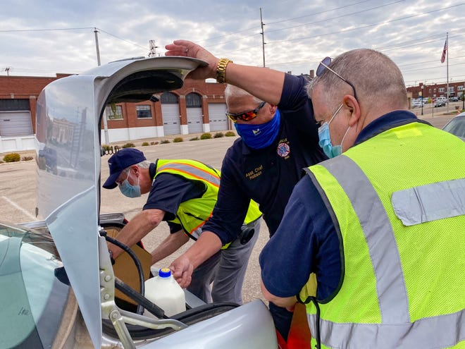 Doug Hobson loads milk into a car at an Oct. 21 food distribution event at Secrest Auditorium.
