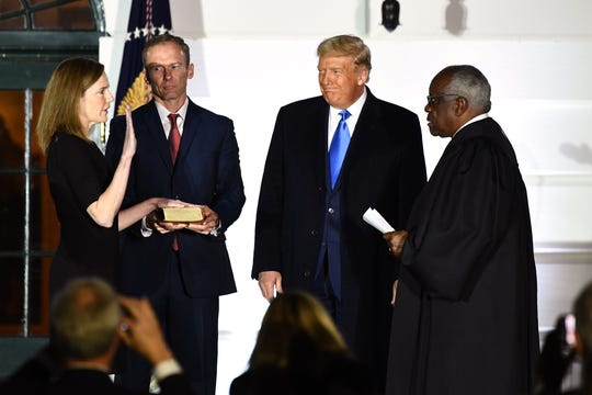 President Donald Trump watches as Supreme Court Associate Justice Clarence Thomas swears in Judge Amy Coney Barrett as a US Supreme Court Associate Justice on Oct. 26, 2020, in Washington, DC.