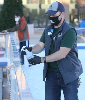 Cuyahoga Falls city employee Jason Pullin sanitizes the handrails at the downtown Cuyahoga Falls ice rink on Saturday.