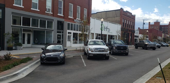 A line of cars are parked along Main Street in Ardmore on Small Business Saturday.