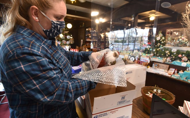 Rachel Derrane wraps a Santa in bubble wrap as she fills an online order and readies it for shipping from the Christmas Joy gift shop along Route 28 in South Chatham. The family business restored online sales during the pandemic to stay afloat.