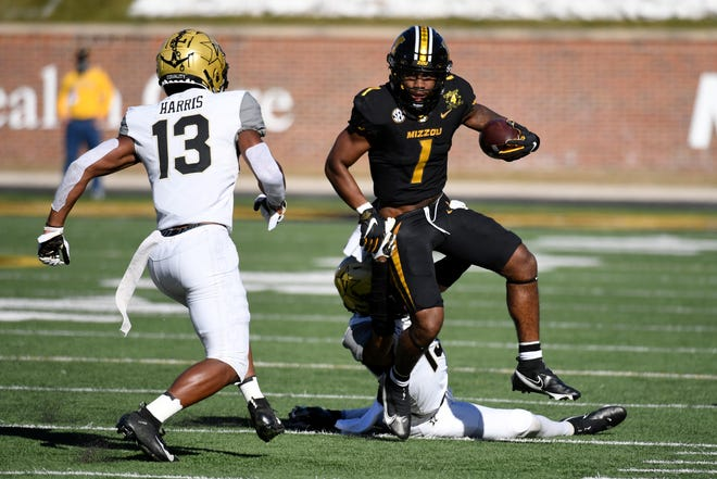Missouri running back Tyler Badie (1) runs with the ball as Vanderbilt safety Brendon Harris (13) and cornerback Elijah Hamilton defend during a game Saturday at Faurot Field.