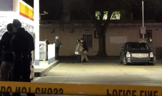 Columbus police and homicide investigators go over the scene of a fatal shooting Friday at a Shell gas station on the South Side.